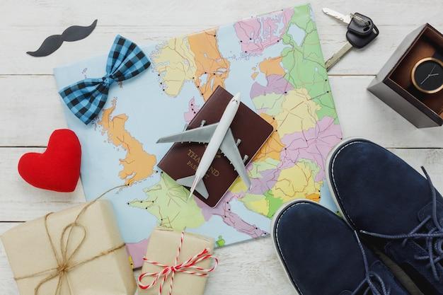 Draufsicht happy father day mit reisekonzept. flugzeug und pass auf karte und rustikalen hölzernen hintergrund. zubehör mit rotem herz, schnurrbart, vintage fliege, schlüssel, geschenk, schuhe, uhr.