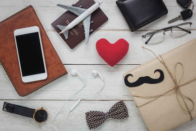 Draufsicht happy father day mit reisekonzept. rote herzform auf rustikalen hölzernen hintergrund. zubehör mit schnurrbart, vintage-fliege, schlüssel, geschenk, weißer handy, kopfhörer, uhr und notebook.