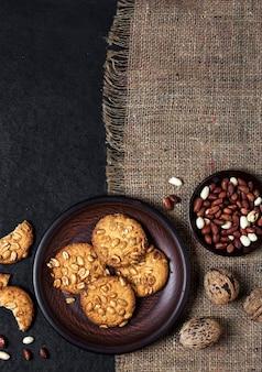 Draufsicht hausgemachte erdnusskekse auf einem braunen teller mit rohen erdnüssen