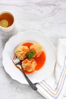 Draufsicht hausgemachtes fried chicken oder shrimp meatball (bakso goreng bandung) mit würziger roter sauce. serviert auf weißem teller mit einer tasse zitronentee.