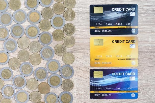 Draufsicht hausmodell und münzen mit kreditkarte auf holztisch unter verwendung als immobilien- und finanzkonzept