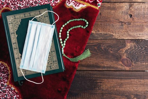 Draufsicht heiliges buch koran, rosenkranz, medizinische maske auf rotem teppich auf braunem hölzernem hintergrund, ramadan-konzept, heiliger monat unter quarantäne, kopienraum