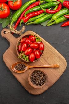 Draufsicht heiße rote und grüne paprikaschoten und tomaten lorbeerschalen mit kirschtomaten und schwarzem pfeffer und löffel auf einem schneidebrett auf schwarzem grund