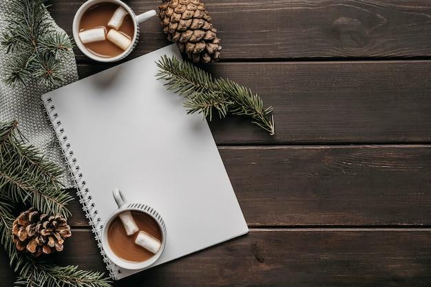 Draufsicht heiße schokoladenbecher mit leerem notizbuch und kopierraum