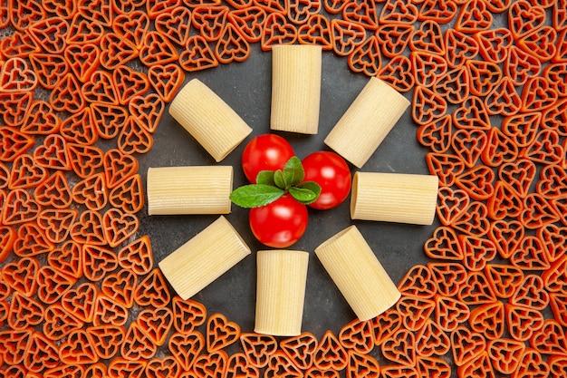 Draufsicht herzförmige italienische pasta rigatoni und kirschtomaten auf dunklem tisch