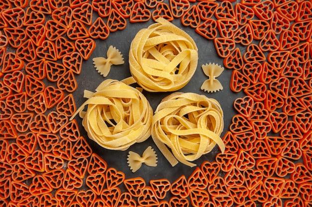 Draufsicht herzförmige italienische pasta tagliatelles und farfalles auf leerem platz auf dunklem tisch