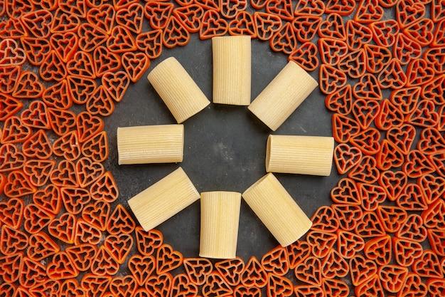 Draufsicht herzförmige italienische pasta und rigatoni auf dunklem tisch