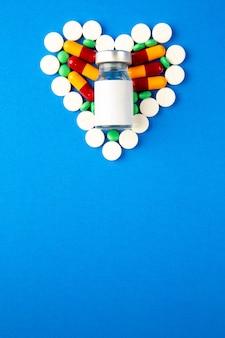Draufsicht herzförmige pillen verschiedenfarbig mit impfstoff auf blauem hintergrund