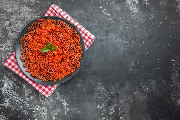 Draufsicht herzförmige rote italienische pasta auf schwarzem ovalem teller auf küchentuch auf dunklem tischfreiraum