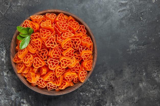 Draufsicht herzförmige rote italienische pasta in einer schüssel auf dunklem tisch mit freiem platz