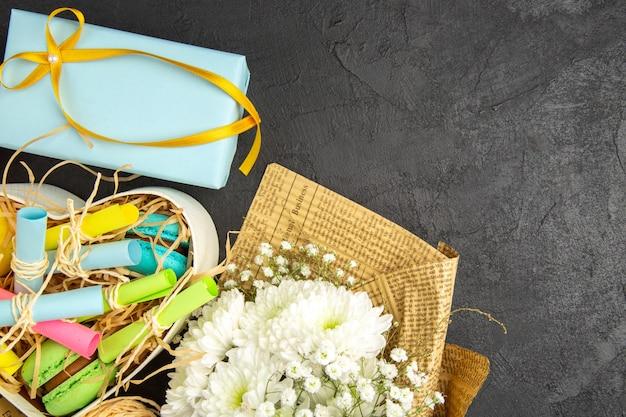 Draufsicht herzförmige schachtel mit aufgerollten haftnotizen und macarons blauem geschenkblumenstrauß auf dunklem hintergrund freier raum