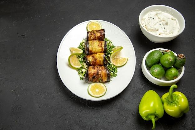 Draufsicht herzhafte auberginenrollen gekochtes gericht mit zitronenscheiben und feijoa auf dunkler oberfläche abendessen ölkochgericht