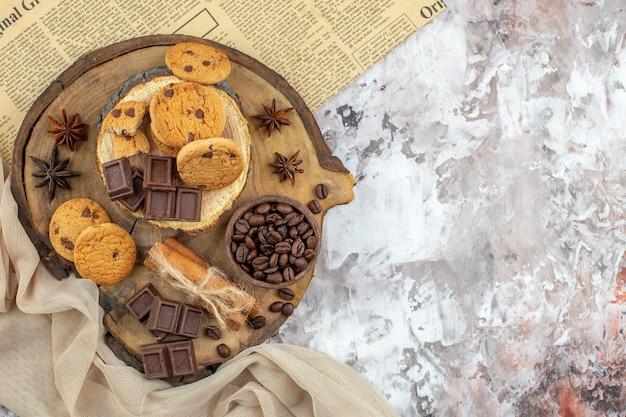 Draufsicht holz rustikales brett mit keksschale mit gerösteten kaffeebohnen schokoladen-zimt-sticks auf tisch mit kopierraum
