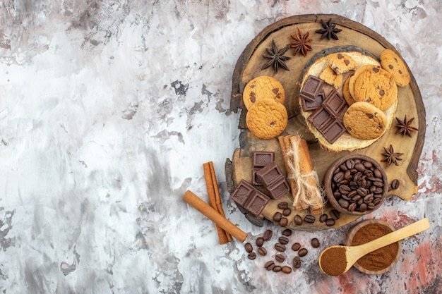 Draufsicht holz rustikales brett mit keksschale mit gerösteten kaffeebohnen schokoladenkakaoschale zimtstangen auf dem tisch mit freiem platz