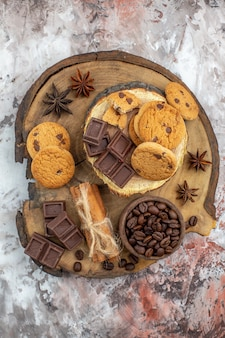 Draufsicht holz rustikales brett mit keksschale mit gerösteten kaffeebohnen schokoladenkakaoschale zimtstangen auf dem tisch
