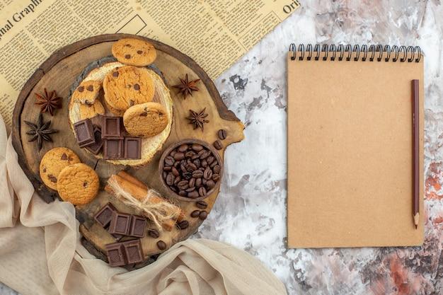 Draufsicht holz rustikales brett mit keksschale mit gerösteten kaffeebohnen schokoladenkakaoschale zimtstangen notizbuch und bleistift auf dem tisch