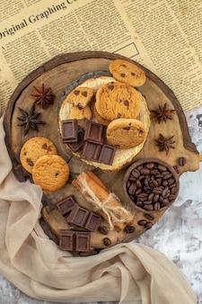 Draufsicht holz rustikales brett mit keksschale mit gerösteten kaffeebohnen schokoladenkakaoschale zimtstangen zeitung auf dem tisch