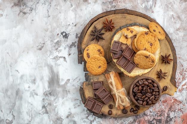 Draufsicht holz rustikales brett mit keksschüssel mit gerösteten kaffeebohnen schokoladenkakaoschale zimtstangen auf dem freien tischplatz