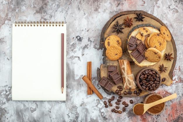 Draufsicht holzbrett mit schüssel mit gerösteten kaffeebohnen schokolade zimtstangen kekse notizbuch und bleistift auf dem tisch