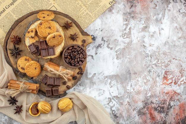 Draufsicht holzbretter mit keksschale mit gerösteten kaffeebohnen schokoladen-zimt-sticks auf tisch mit kopierplatz