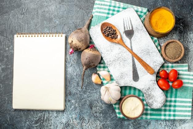 Draufsicht holzlöffel auf schneidebrett gewürze in schalen kirschtomaten knoblauchrüben notebook auf grauem tisch