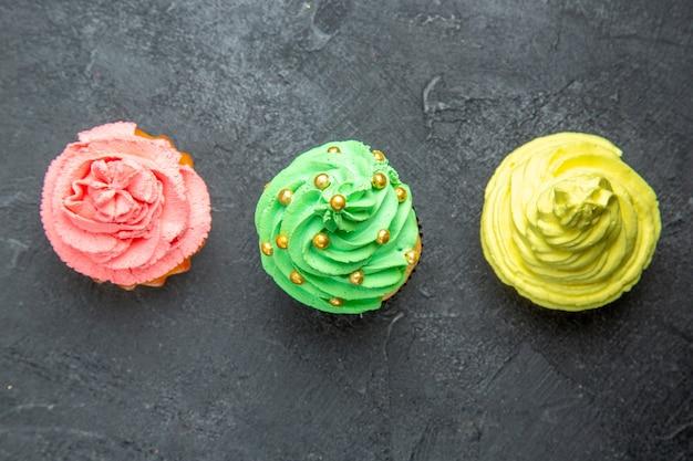 Draufsicht horizontale reihe mini bunte cupcakes auf dunkler oberfläche