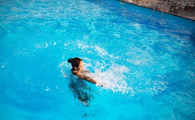 Draufsicht hübsches junges mädchen, das glücklich im blauen klaren wasser im pool unter den strahlen des hellen sonnenlichts spritzt. konzept der entspannung im hotel und auf see. platz für werbung