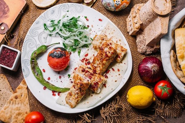 Draufsicht hühnchen-lula-kebab auf fladenbrot mit tomate und gegrilltem pfeffer mit zwiebeln und kräutern