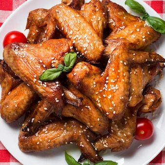 Draufsicht hühnerflügel auf teller mit sesam und kirschtomaten