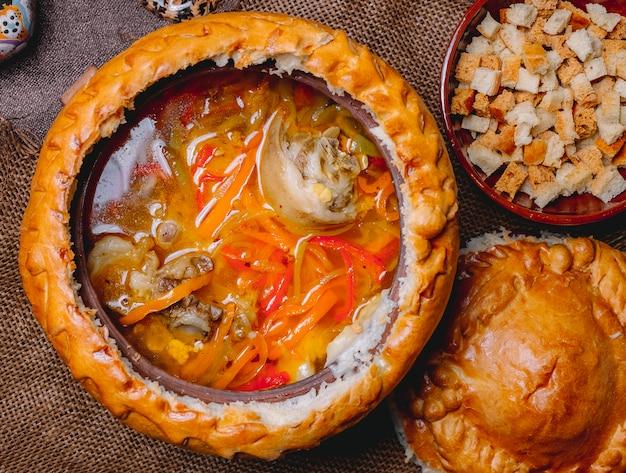Draufsicht hühnersuppe in einem tonkrug mit crackern und einem teigdeckel