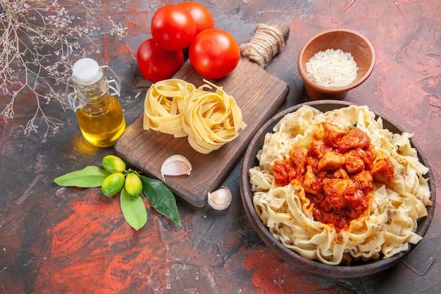 Draufsicht huhn mit teig nudelgericht mit tomaten auf dunkler oberfläche teig nudelmehl