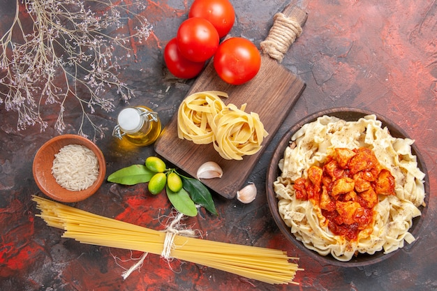 Draufsicht huhn mit teig nudelgericht mit tomaten auf dunkler oberfläche teig nudeln essen
