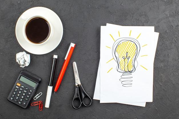 Draufsicht ideallight glühbirne zeichnung auf notizblock schere taschenrechner tasse tee roter stift und schwarzer marker auf schwarz
