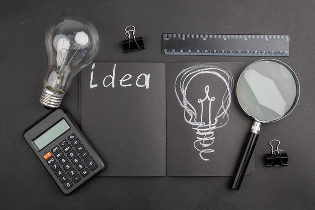 Draufsicht idee auf schwarzem notizblock geschrieben glühbirne binder clips lupa lineal rechner auf dunkelheit