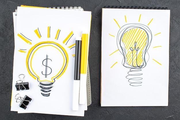 Draufsicht ideenglühbirnen auf notebooks gelbe und schwarze markierungen schwarze binderclips auf schwarzer oberfläche