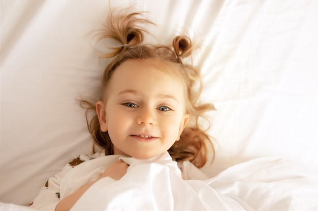 Draufsicht im bett bequeme matratze weiße decke bettwäsche liegt kind hat breites lächeln schaut kamera kind guten morgen