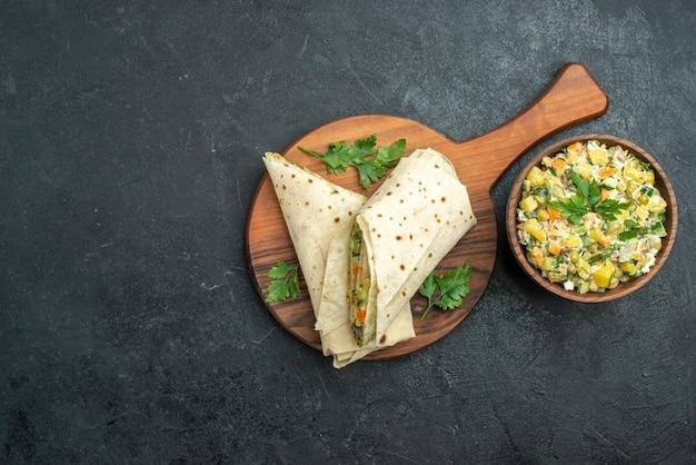 Draufsicht in scheiben geschnitten leckeren shaurma mit mayyonaise-salat auf grauer oberfläche salat burger sandwich essen snack