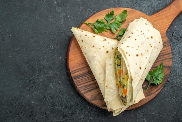 Draufsicht in scheiben geschnittenes shaurma leckeres salatsandwich auf grauem burger-pita-sandwich-brotsalat