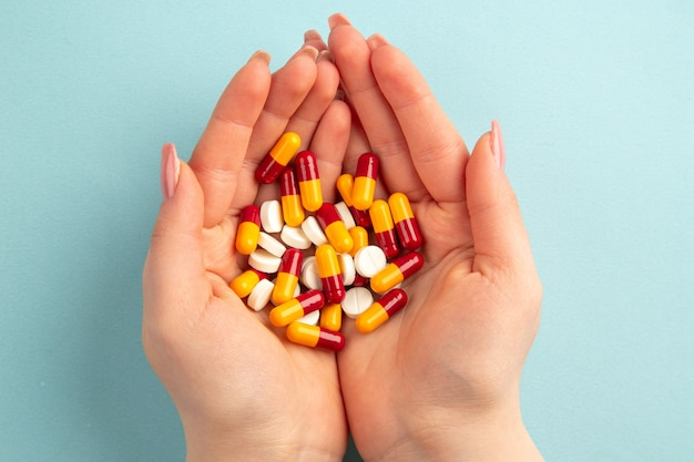 Draufsicht junge frau mit pillen in ihren händen auf blauem hintergrund pandemie covid-virus gesundheitslabor wissenschaft krankenhaus farbe