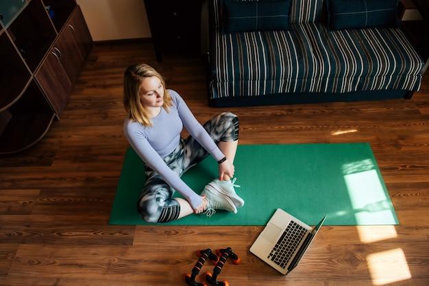 Draufsicht: junge hübsche frau, die eine strecke macht, die zu hause auf yogamatte sitzt