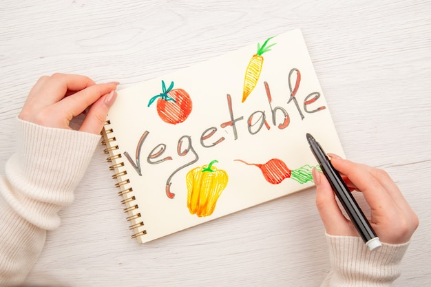 Draufsicht junges weibliches schreiben und zeichnen auf notizblock auf weißem schreibtisch