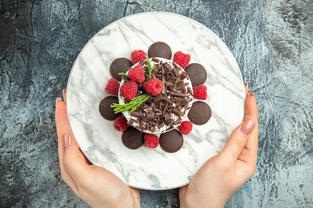 Draufsicht-käsekuchen mit schokolade auf ovalem teller in frauenhänden auf grauer oberfläche