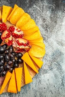 Draufsicht käsescheiben trauben und granatapfel auf ovalem servierbrett auf dunklem hintergrund