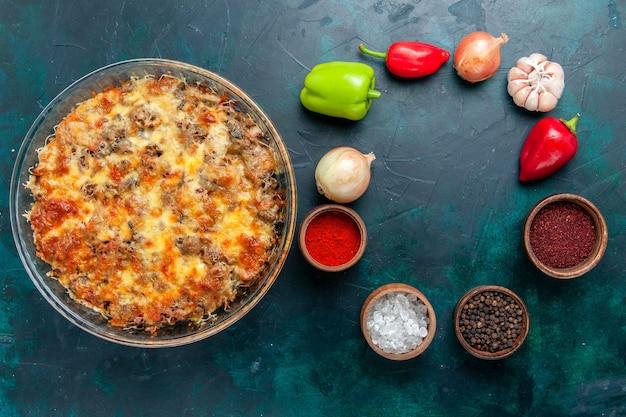 Draufsicht käsiges fleischmehl mit frischem gemüse und gewürzen auf dunkelblauem hintergrundnahrungsmittelfleischmahlzeitgericht gemüsedinner