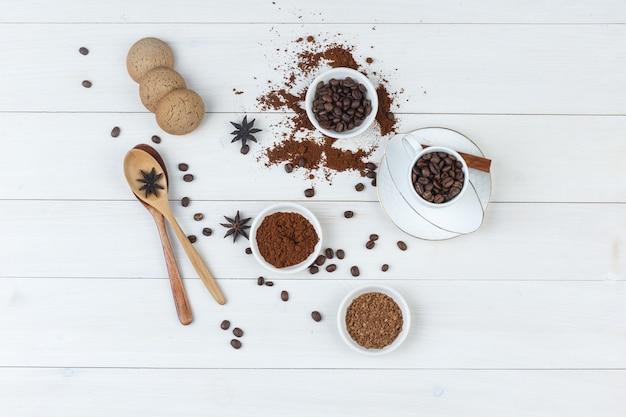 Draufsicht kaffeebohnen in tasse und schüssel mit gemahlenem kaffee, gewürzen, keksen, holzlöffeln auf hölzernem hintergrund. horizontal