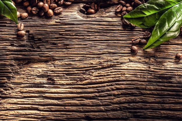Draufsicht kaffeebohnen und grüne blätter auf rustikalem eichentisch.