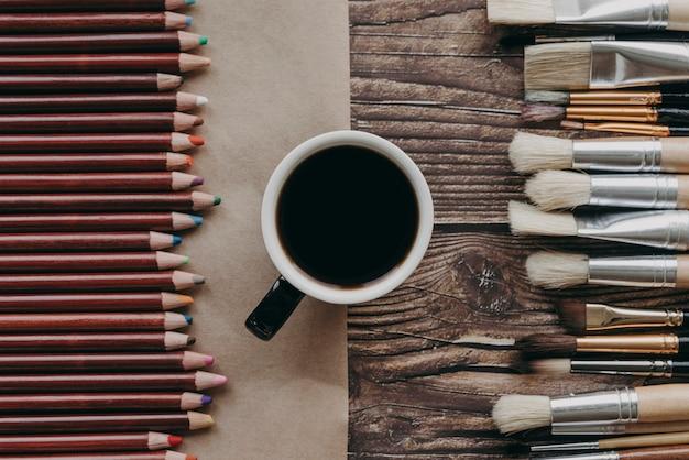 Draufsicht kaffeetasse, bürsten und buntstifte