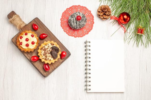 Draufsicht kakao- und beerentörtchen und kornelkirschen auf dem schneidebrett-kakaokuchen und den kiefernblättern mit weihnachtsspielzeug und einem notizbuch auf dem weißen holzgrund