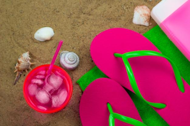 Draufsicht kaltes cocktail, hausschuhe und sonnencreme auf einem grünen tuch auf einer biene
