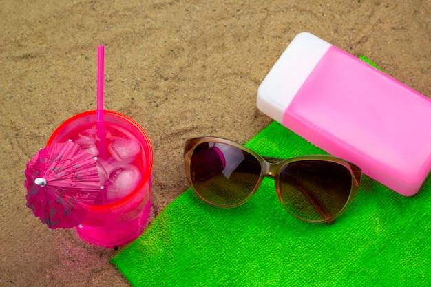 Draufsicht kaltes cocktail, sonnenbrille und sunblocker auf einem grünen tuch auf einer biene